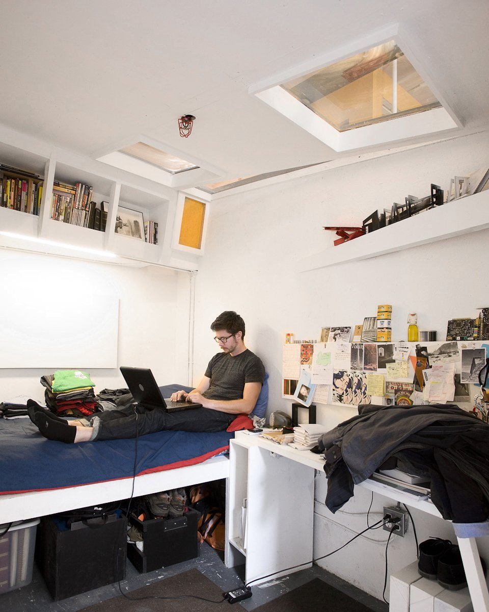 """Justin Smith's cell-like quarters are packed full of books and art. """"Each room gets the bare minimum: a sleeping area, a desk, and storage,"""" explains Ionescu. The designers carefully laid out the space so that the beds in each room are as far apart from each other in plan as possible, in order to get as much privacy as possible.  Photo 5 of 13 in Communal Living on a Budget in Brooklyn"""