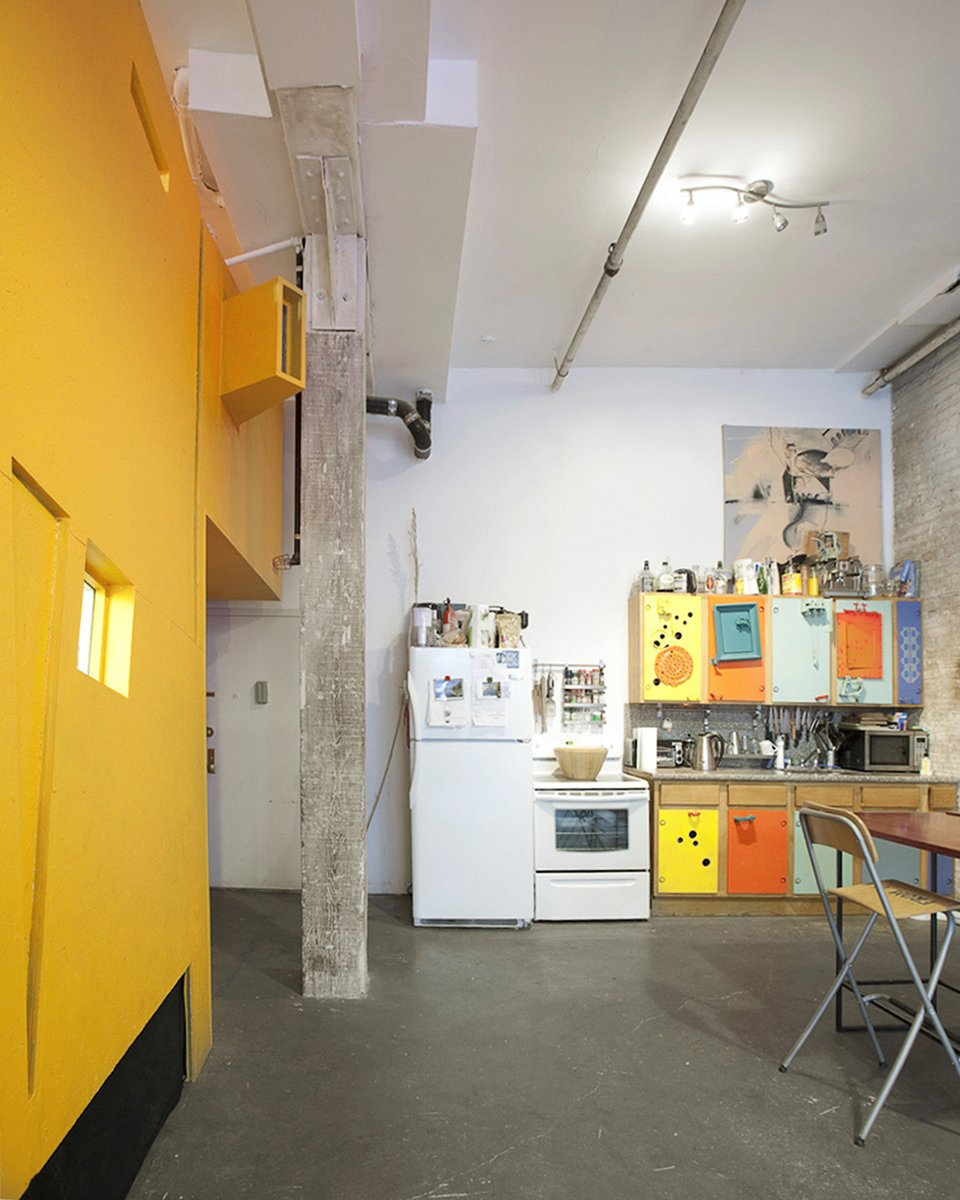 """Confining The Miner and A Major to just one side of the loft allowed the roommates to leave the kitchen, dining, and living areas wide open. This makes it great for parties. """"We wanted it to be fun, community-oriented, and playful—like the Situtationist's credo where work is play,"""" says Ionescu. """"It's an experiment. It works because we are all friends. I don't think strangers could live in this manner.""""  Photo 11 of 13 in Communal Living on a Budget in Brooklyn"""