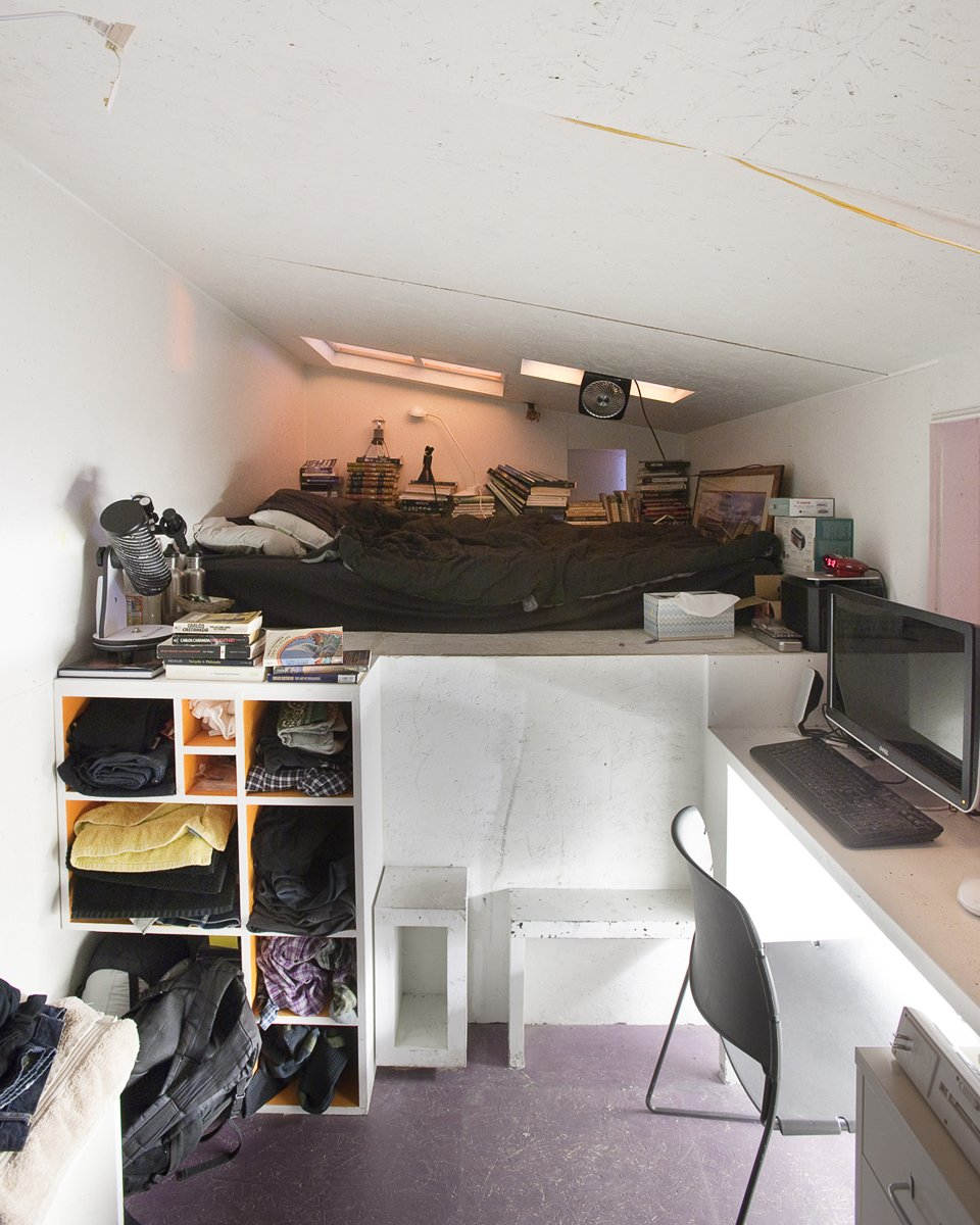 Located at the rear corner of the installation, down a progressively narrowing hallway, and reached by a steep staircase, Eric Juron's attic-like space is the most remote of the bedrooms. A window over his desk looks down through the gap between the Major and the Minor.  Photo 12 of 13 in Communal Living on a Budget in Brooklyn