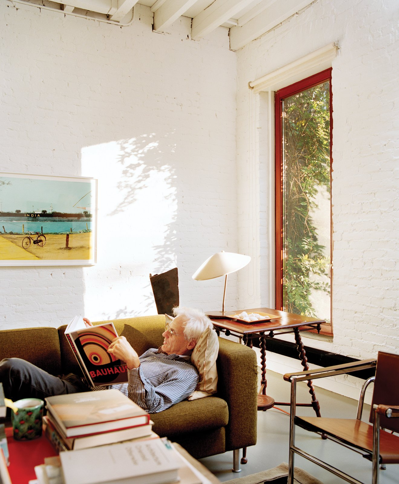 """Living Room, Sofa, Chair, and Concrete Floor """"When I first thought of moving to Harlem, I looked at a map,"""" says Ryall. """"The island's about 210 blocks long, I'm near 110th Street—I thought, 'It's right in the center of Manhattan.'""""  Photo 5 of 11 in 10 Charming Brick Interiors from Manhattan"""