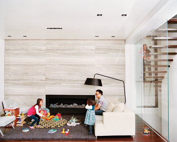 When the Hsus found themselves expecting a third child, they engaged Lang to enclose the upper part of their double-height living room to create a fourth bedroom and playroom-study upstairs. Additionally, Lang resurfaced the fireplace wall with massive slabs of filled silver travertine marble. The slabs were so large that one of them broke an adjoining floor-to-ceiling glass pane during installation.