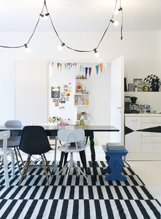 The family's activity centers around the open-plan dining room, which does triple-duty as a living room and kitchen. Susanna prefers a motley set of dining chairs over a coordinated set; that way guests can pick their favorite when they sit.