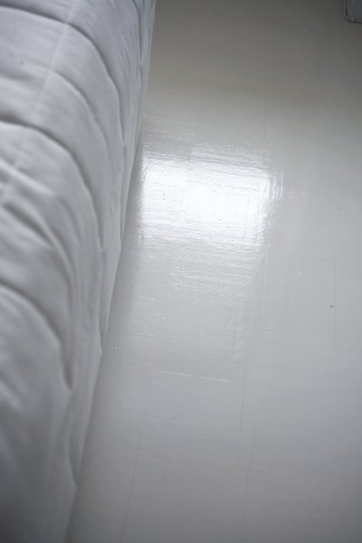 """It took Susanna several layers of sanding—and then finally tossing her water-based paint and selecting the proper oil-based formula—to get the floor as white as she'd envisioned. But she couldn't be happier with the result.  """"The apartment looks bigger when there are white surfaces for the light to bounce on,"""" she says."""