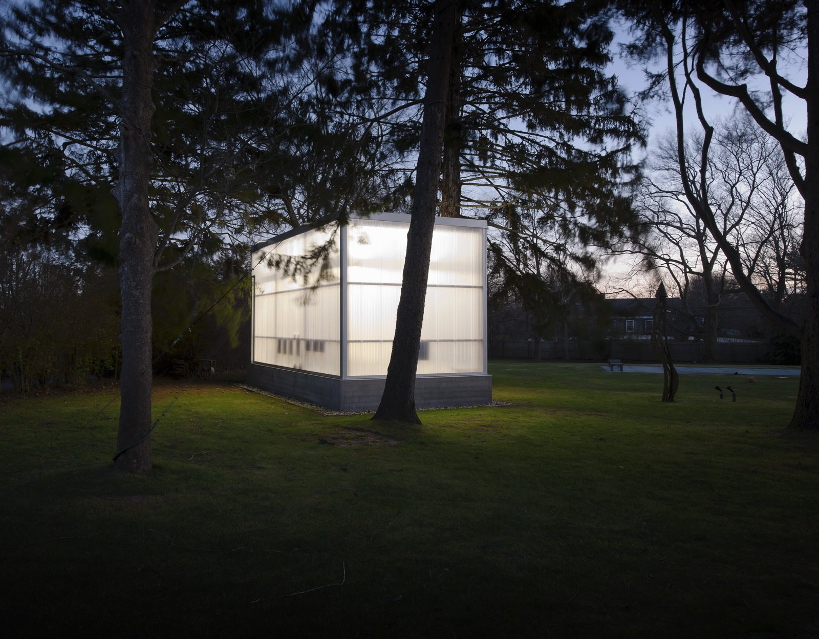 """Completed in 2009, the studio shines in the night among the trees. Weiselberg and Semaan devised a clever foundation system that allowed them to avoid ripping up roots. """"The floor is a concrete slab on a steel deck that sits on a spider web of steel beams,"""" Weiselberg says. """"There are eight piers per side of the structure, each designed so that if we dug the 12-inch hole and there were roots underneath, we could move it along a certain radius. The base is like a skirt that is just hanging off the building."""" So while the floor floats a foot above the ground in the couple's backyard for now, it could one day easily be picked up and moved elsewhere.  McWhorter Vallee Design Inc.'s Favorites from His-Her Collage and Ceramics Studio"""