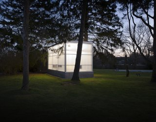 "Completed in 2009, the studio shines in the night among the trees. Weiselberg and Semaan devised a clever foundation system that allowed them to avoid ripping up roots. ""The floor is a concrete slab on a steel deck that sits on a spider web of steel beams,"" Weiselberg says. ""There are eight piers per side of the structure, each designed so that if we dug the 12-inch hole and there were roots underneath, we could move it along a certain radius. The base is like a skirt that is just hanging off the building."" So while the floor floats a foot above the ground in the couple's backyard for now, it could one day easily be picked up and moved elsewhere."