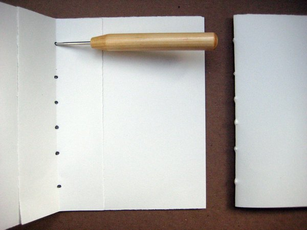 Line the template up against each signature and use the awl to poke holes at each mark that you've made, all along the fold. This will ensure that the holes line up when you are threading the pages.