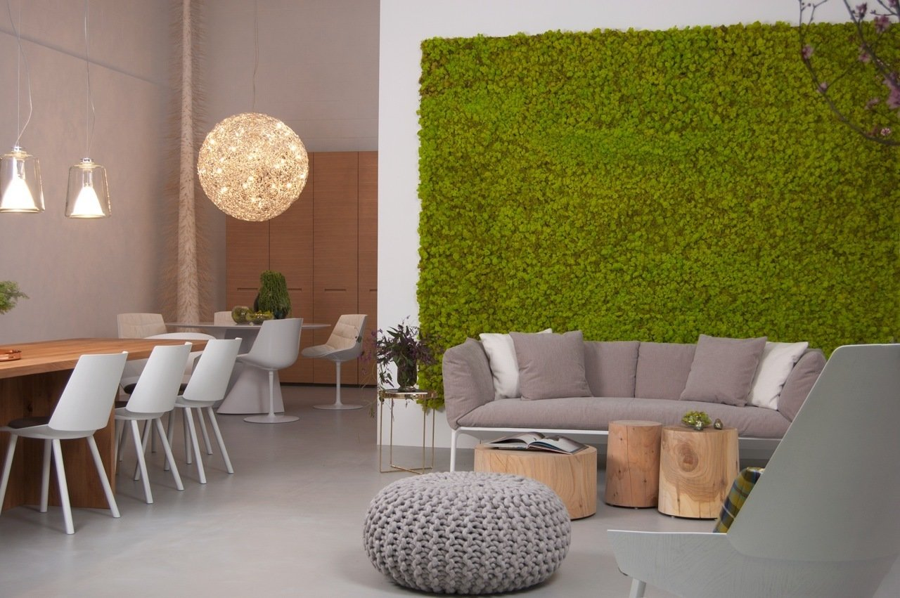 """The eight-foot-high live vertical moss wall is a bright backdrop for the Yale sofa. On the left is the Zehn table in oiled European oak by Phillip Mainzer for e15, lit by """"Lanterna"""" hanging light fixtures by Oluce. The dining chairs are """"Houdini"""" side chairs with upholstered seats by Stefan Diez for e15.  Supernatural San Francisco by Jaime Gillin"""