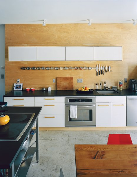 Concrete floors and an Ikea kitchen and spice rack make for an affordable, cleanly geometric aesthetic at the back of the bottom floor. The appliances are by Frigidaire, and the black countertops are sealed with Eco Tuff by Eco Procote.