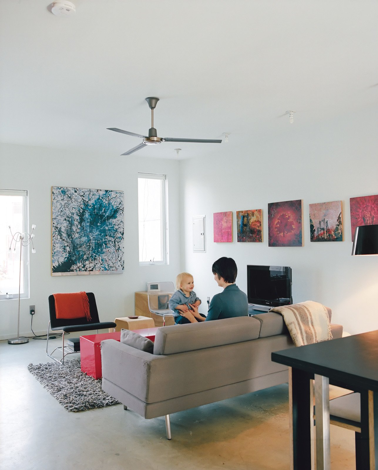 Courtney and Teague play in the living room opposite a Perch lounge designed by Eric Pfeiffer for Offi. The paintings behind the TV are by artist Chris Clark.  Photo 9 of 11 in Green Urban Housing in Philadelphia