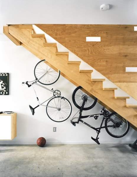 """More adult playthings, like this pair of bikes live under the stairs, whose cutouts break up the plane of plywood and double as peepholes for kids at play.  Photo 6 of 9 in """"Where Should I Keep My...?"""": Solving the Ultimate Small Space Dilemmas"""