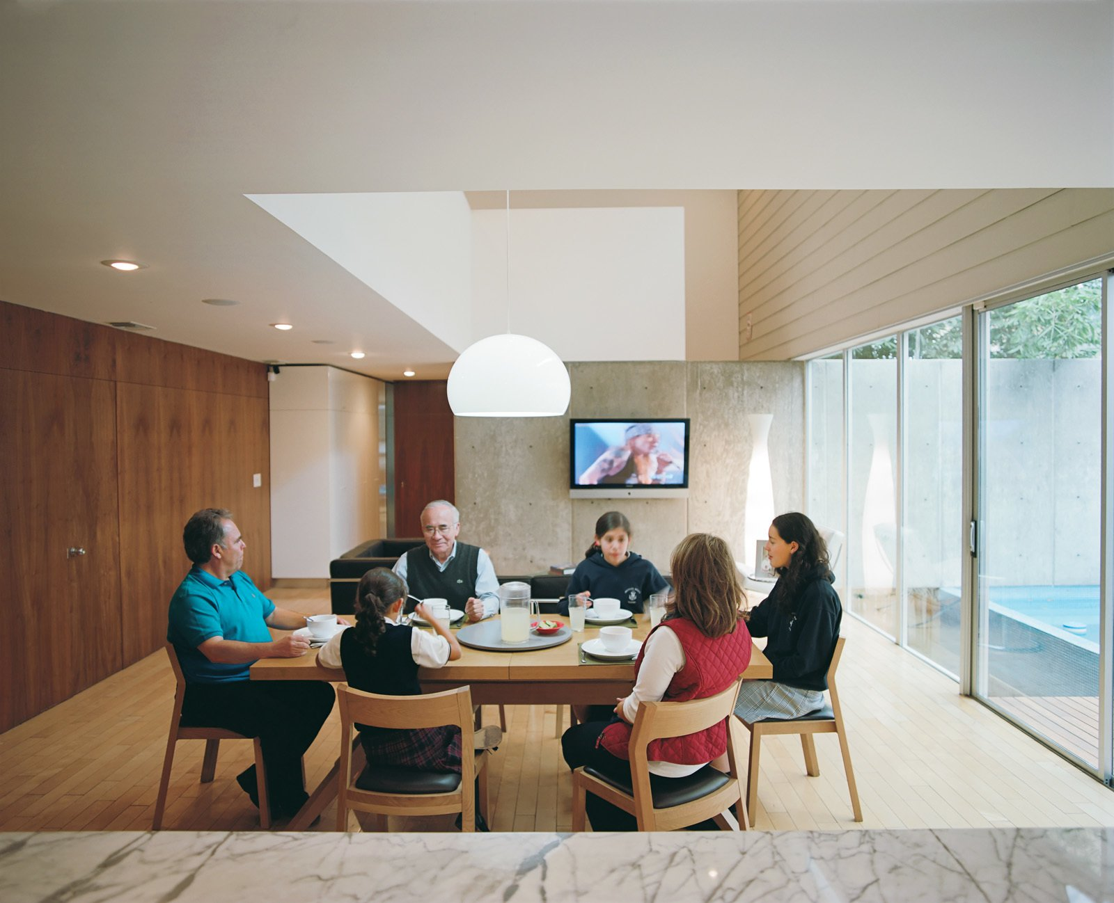 Dining Room, Chair, Table, and Pendant Lighting Marco Becerril, at the left end of the table, presides over his extended family in the double-height dining area.  Photo 6 of 13 in Modern in Tijuana