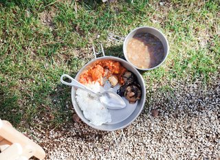 Food is served in traditional camping cookware.