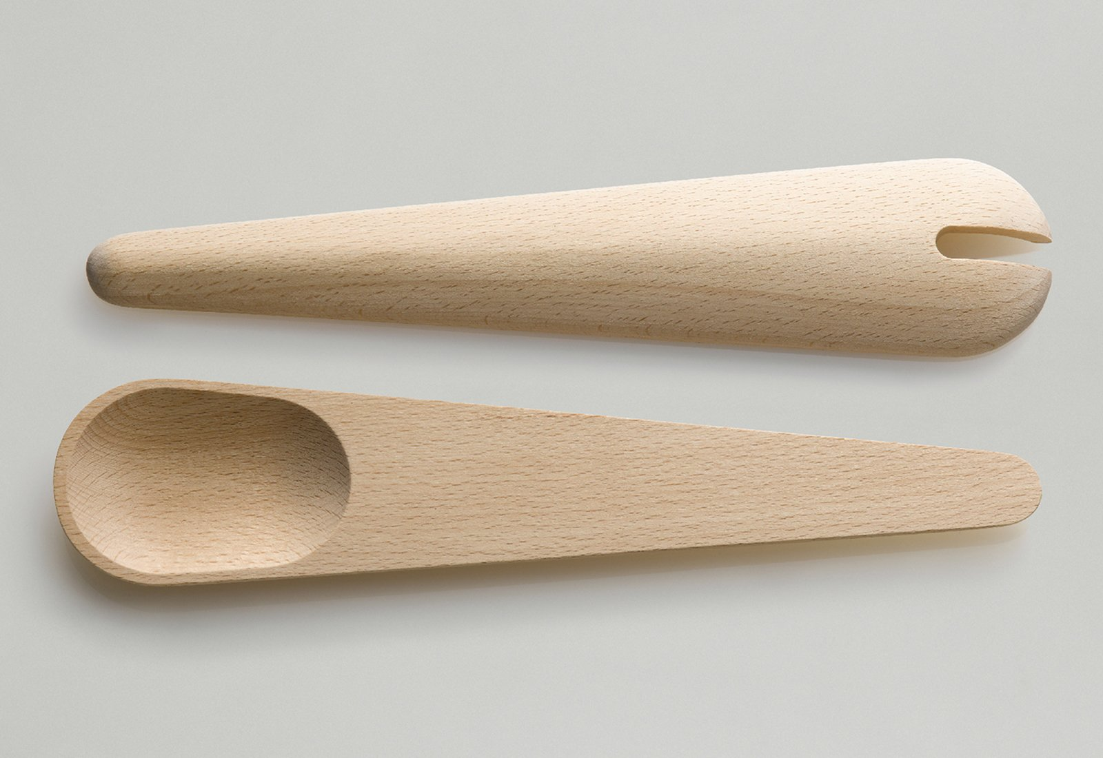 The Toss Around spoons differ from the Hang Around set as they are both spoons (rather than one spoon and one spatula), lack the slat in the back, and feature shallower spoons with a notch in one.  Photo 3 of 5 in Hang Around and Toss Around