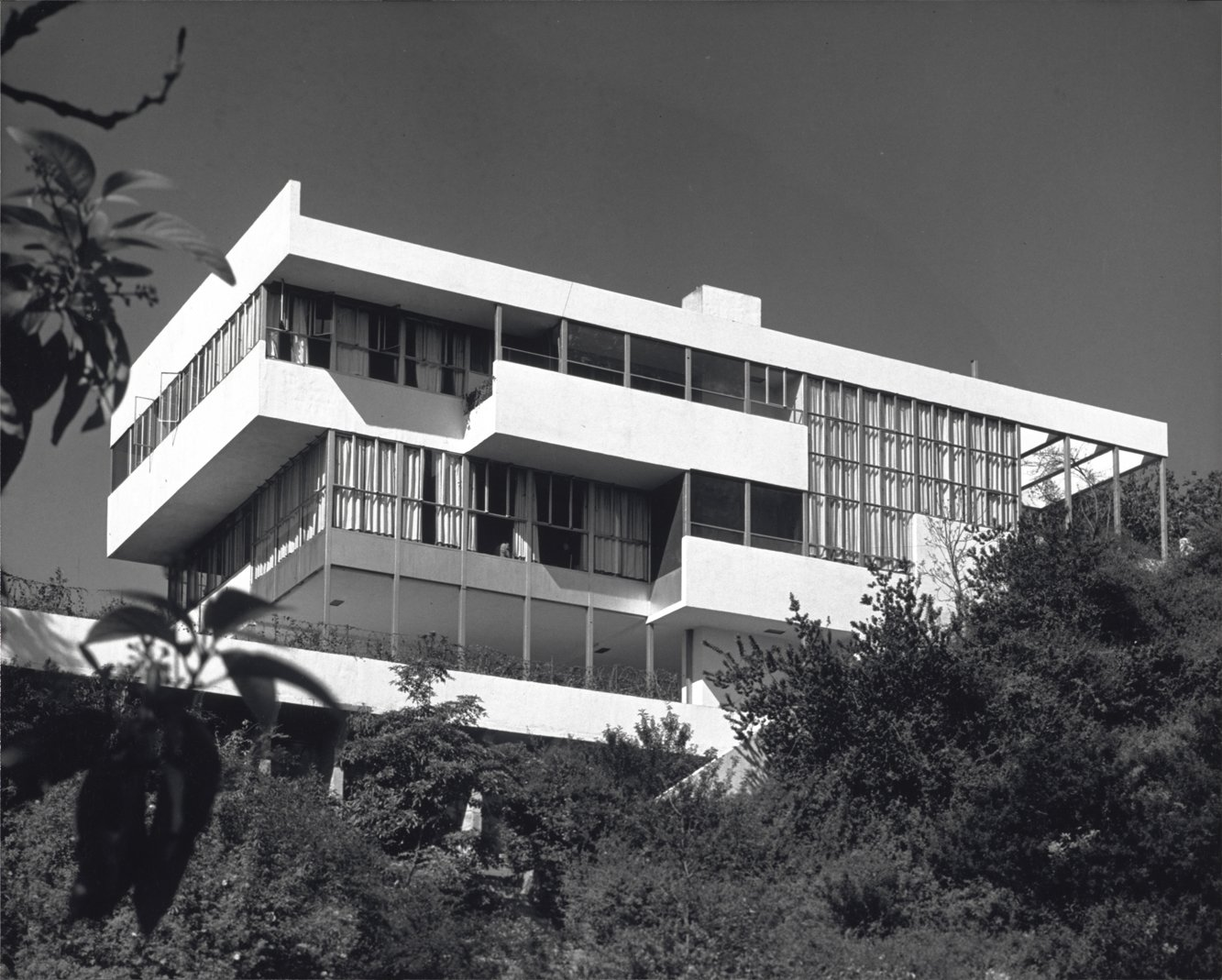 """Exterior, Flat RoofLine, House Building Type, and Glass Siding Material The owners of the 1929 Lovell Health house agreed to a rare tour of their home as part of the 85th anniversary celebration.  Photo by Julius Shulman, courtesy Getty Institute.  Don't miss a word of Dwell! Download our  FREE app from iTunes, friend us on Facebook, or follow us on Twitter!  Photo 6 of 16 in 10 Modern Homes That Made a Star Appearance in Films from Mills & McGregor on """"Beginners"""""""