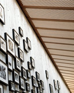 Framed family photos hang, clustered and skylit, in the corridor.
