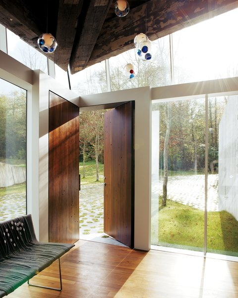 While most homes have their front doors centered on a flat wall, this home in Canada by Omer Arbel is entered through two solid walnut doors at the corner of the home.