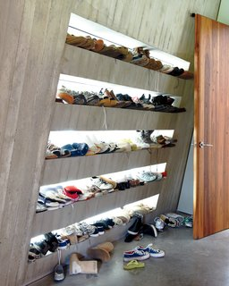 Just off an internal courtyard, a mudroom provides a prime place to keep sneakers. Each family member has their own shelf, backlit by windows that illuminate every pair.