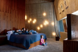 """Arbel's """"14"""" sconces spot the wall to ethereal effect in the master bedroom. """"I wanted this place to be habitable. One of my greatest criticisms of modern architecture is that it often forgets to make things cozy."""""""