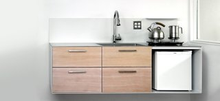 Ideal for small spaces, the Ferro kitchen is a modular and customizable wall-mounted unit, built from powder-coated bent steel plate, heavy gauge stainless steel, and solid wood drawer fronts.