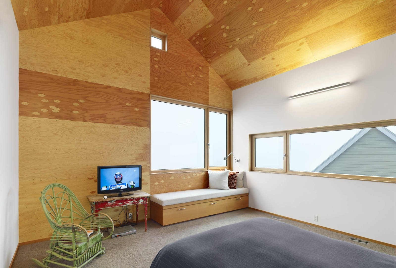 Inside the master bedroom, the juxtaposition of old and new is pronounced. Wooden furniture sits next to a streamlined built-in bench. The wood-framed windows open up to views of the gabled roof.  The Farm by Miyoko Ohtake