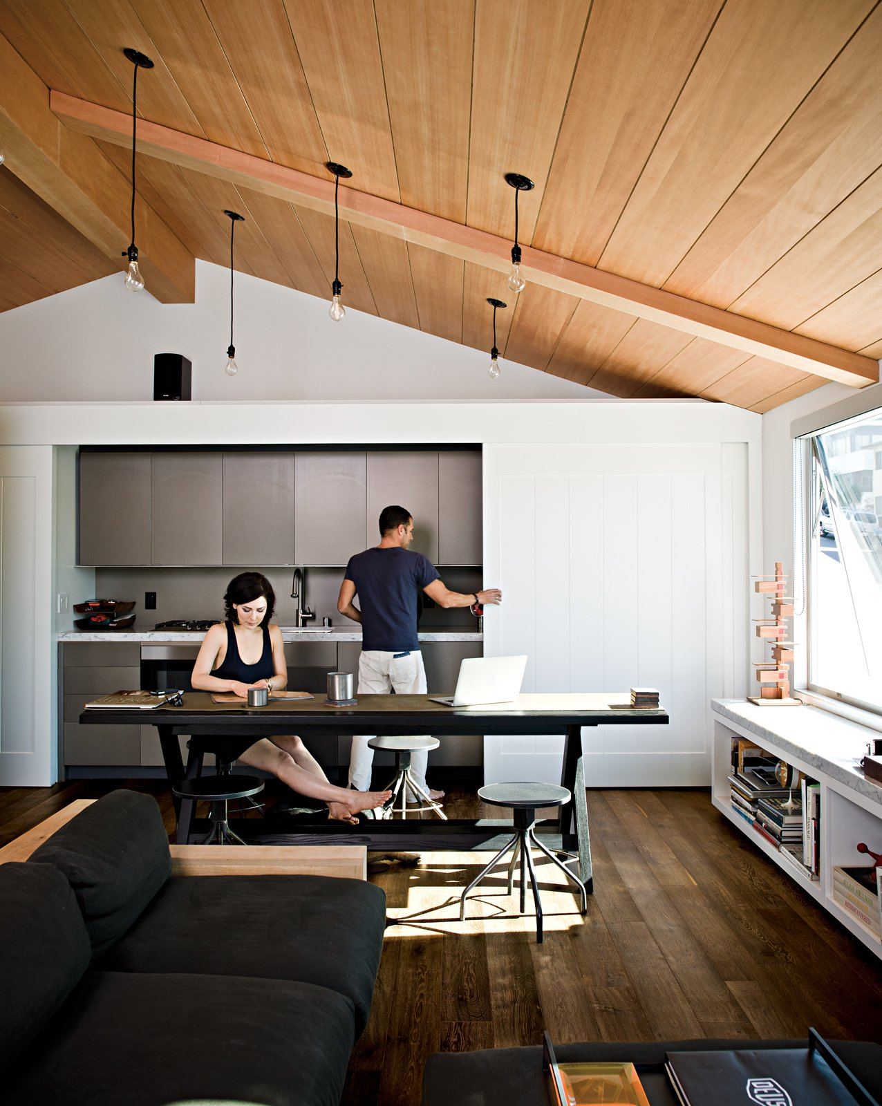 After meals are made, the sliding doors hide the anodized aluminum Miele fixtures, creating a clean, uncluttered look. Tagged: Living Room, Medium Hardwood Floor, Sofa, and Pendant Lighting.  Photo 4 of 18 in Less is More in this Manhattan Beach Bungalow