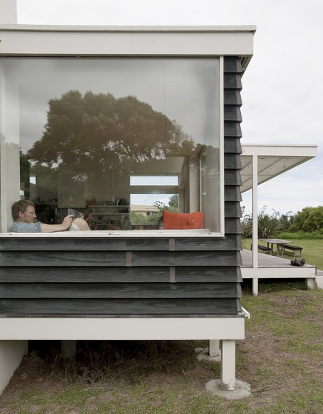The glassy pavilion containing kitchen, dining, and living areas is elevated three feet off the ground on posts so it appears to hover among the dunes.