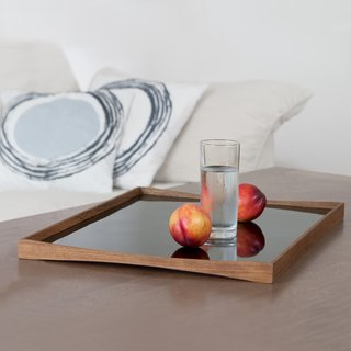 Architect Finn Juhl designed predominantly in the 1940s and 50s and created the TurningTray in 1956 to match the furniture in his house. The curvature of the teak eliminates the need for handles and the two sides—one laminated in black and the other in either red, white, light green, or pale blue—let it transition from day to evening use.