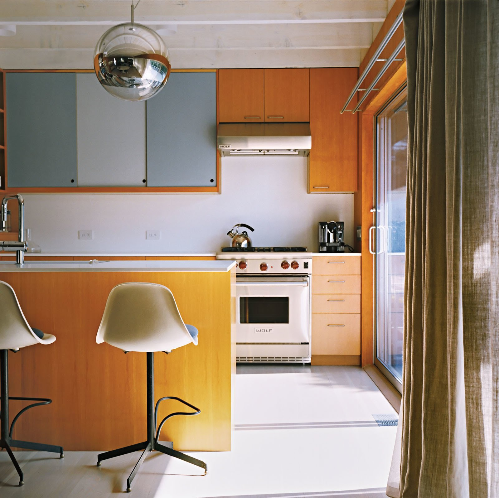 Kitchen, Range, Range Hood, Wood Cabinet, and Pendant Lighting A Mirror Ball pendant by Tom Dixon hovers over the kitchen counter.  Lit from Above from Long Island Found