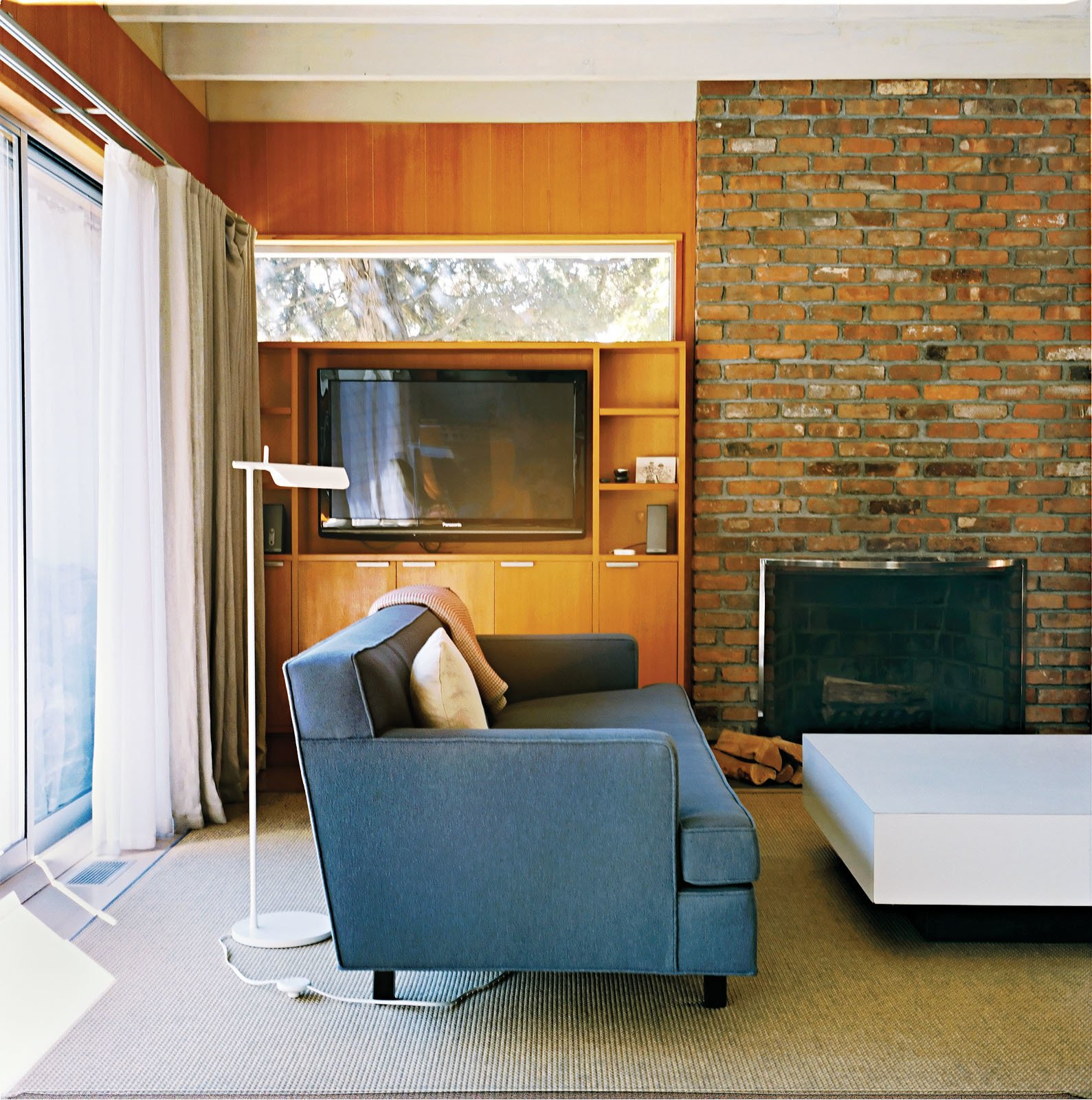 Living Room, Standard Layout Fireplace, Wood Burning Fireplace, Floor Lighting, and Sofa A Tab F1 floor lamp from Flos stands behind the Edward Wormley–designed Dunbar sofa.  Photo 2 of 12 in Long Island Found