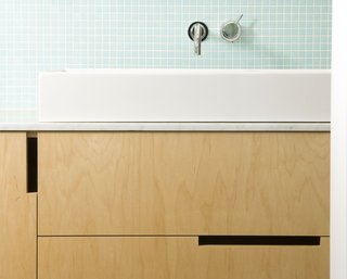 Open rectangular cutouts in modern wood cabinetry were the way to go in this bathroom vanity.