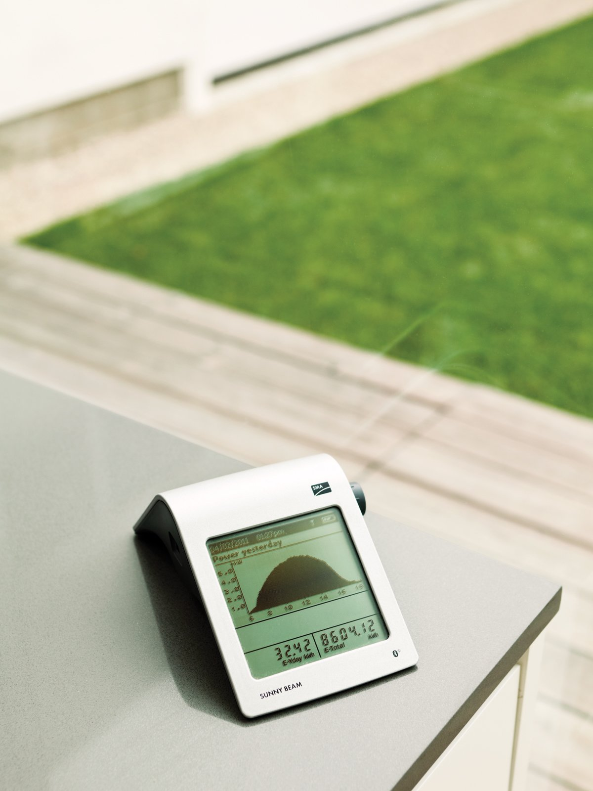 """In the kitchen, an SMA Sunny Beam solar monitor displays the number of kilowatts generated. Though the monitor doesn't display real-time energy consumption, the family often operates in the negative. """"It helps us understand what's going on and seeing it reminds us to be energy-conscious,"""" David says.  Photo 12 of 13 in A Dream House for the Ages"""