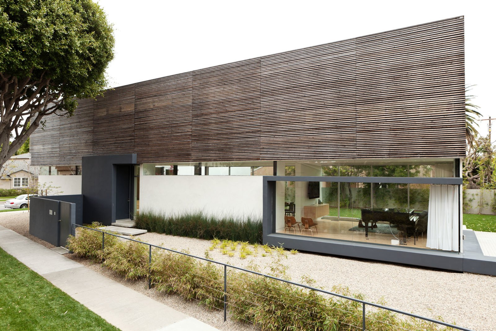 Exterior, House Building Type, Wood Siding Material, and Flat RoofLine The larch rainscreen covering the second floor give the house a light appearance and also provides privacy. Though it's difficult for outsiders to look in, the openings between the slats of wood let the family sneak views to the outside.  Photo 7 of 13 in A Dream House for the Ages