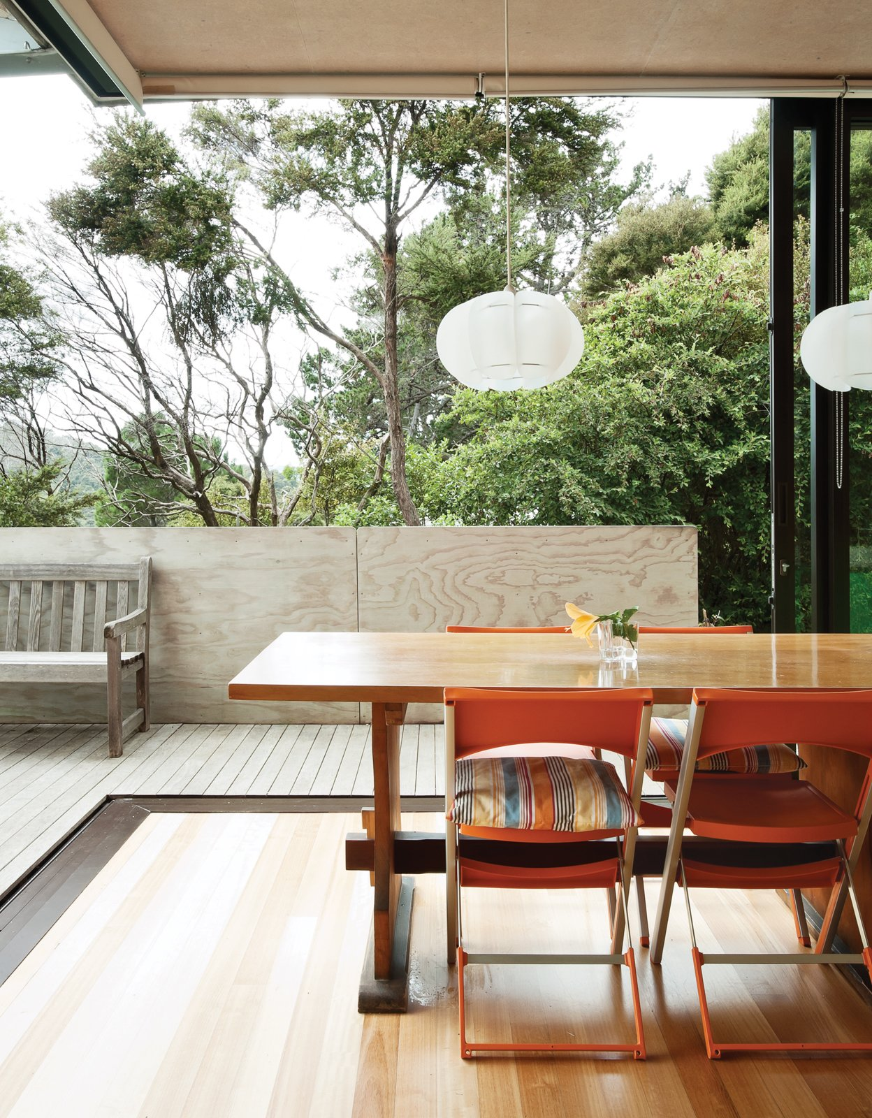 Dining Room, Pendant Lighting, Table, Chair, and Light Hardwood Floor The home's sliding doors blur the boundaries between inside and out.  Photo 9 of 25 in Make Your Parents Happy by Building Them a House
