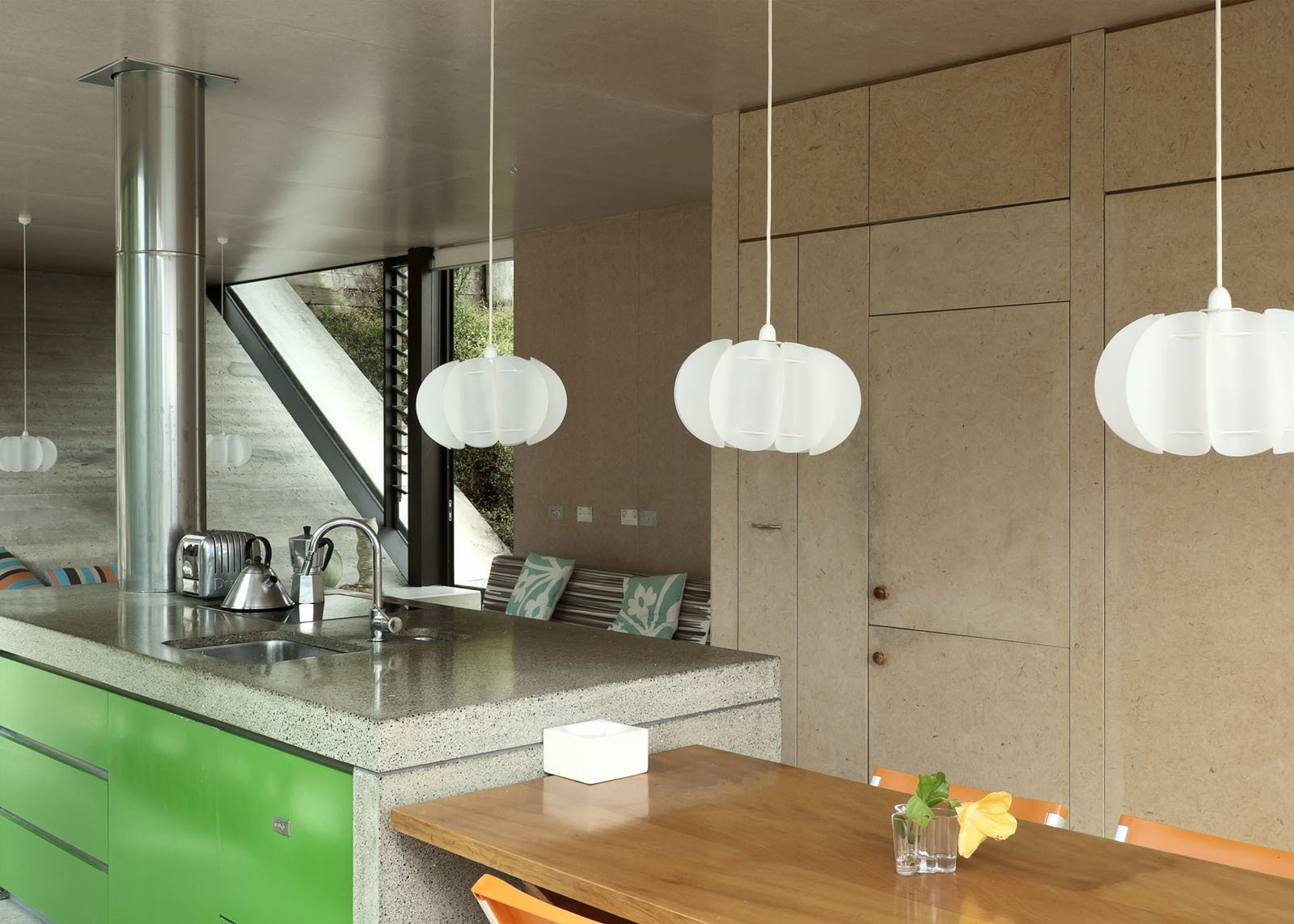 The hanging Iko Iko pendants in the kitchen add a vertical touch to a space and help frame the views outside.  How to Design with Green by Diana Budds from Make Your Parents Happy by Building Them a House
