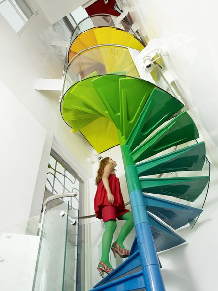 """Staircase and Metal Railing """"The staircase is the hub, the soul of the project,"""" Rogers says. """"It's meant to be enjoyed."""" From the ground, the steps start with the cool colors of the earth, then get warmer as they reach up to the sky.    Photo 5 of 6 in A Family Goes Somewhere Over the Rainbow"""
