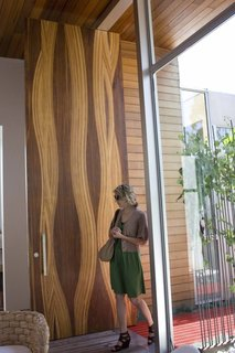 The front door is an awe-inspiring, 14-foot, mixed wood creation made by L.A. custom door fabricators Real Door Inc. The wood used in making the door were mostly leftovers from the shop, says Dino of Real Door Inc. A gentle wave pattern accentuates the material's natural grain.
