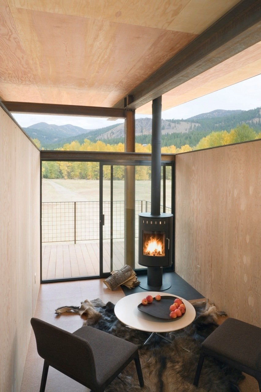 Living Room, Coffee Tables, Chair, and Wood Burning Fireplace Inside a Rolling Hut by Tom Kundig of Olson Kundig Architects, a metal fireplace keeps the compact interior of the chalet cozy.  97+ Modern Fireplace Ideas from Building the Maxon House: Week 18