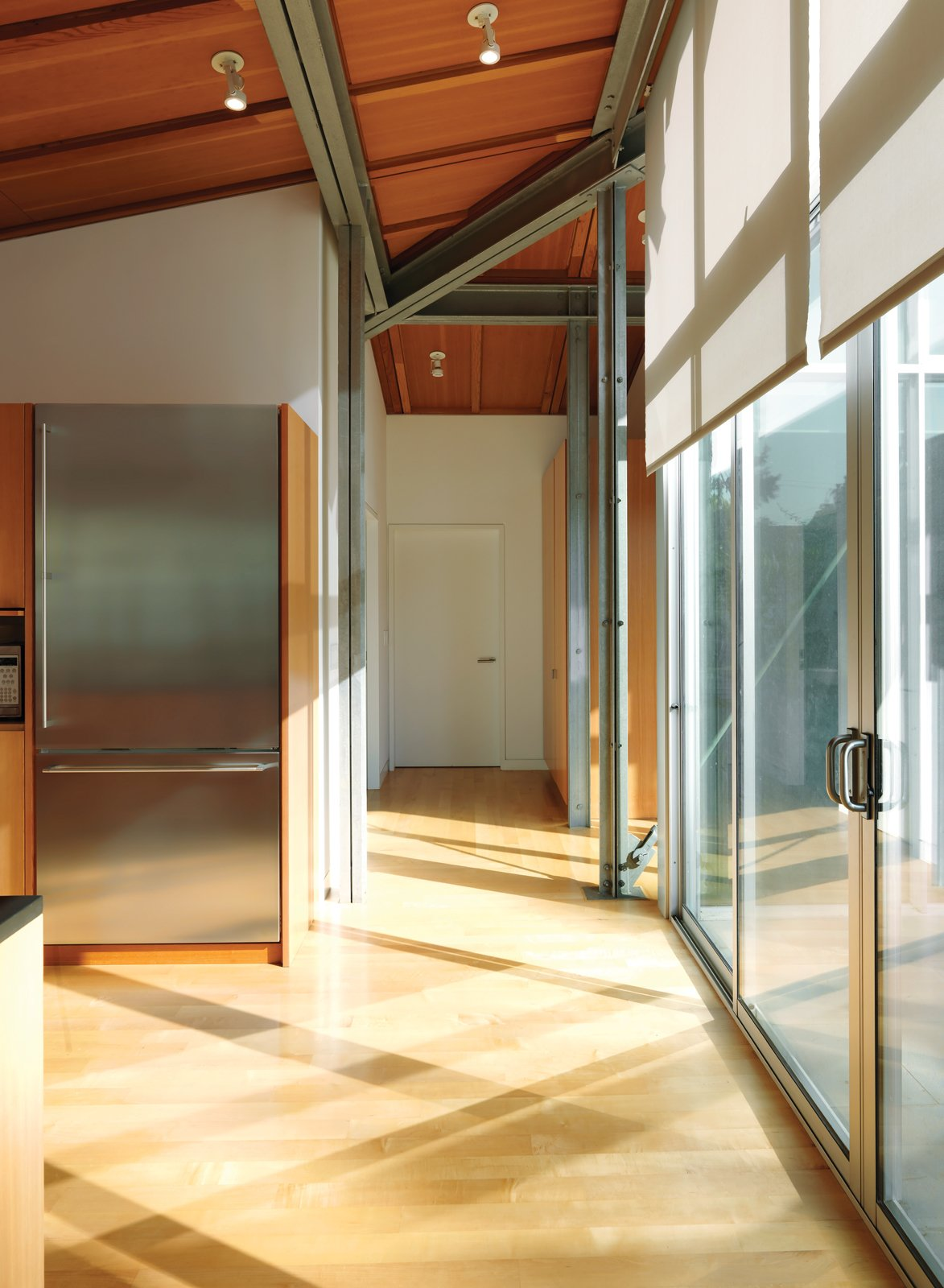 Kitchen, Refrigerator, and Wood Cabinet The architecture mixes Douglas fir beams and exposed steel framing, achieving its soaring spaces without pretentiousness.  Photo 5 of 16 in Family Matters