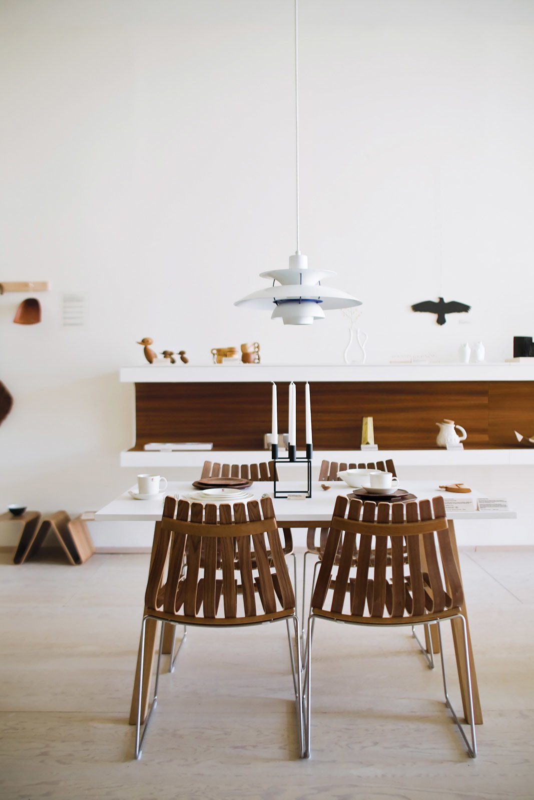 At the shop, Poul Henningsen's PH 5 lamp for Louis Poulsen hangs over the Sandra table by Thomas Sandell for Asplund and Scandia chairs by Hans Brattrud for Fjordfiesta (top left).  In the Home