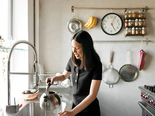 Sherman's friend Anna Chang prepares tea in the kitchen. The range is by Wolf. Walls are coated with parging, a type of concrete made with sand instead of gravel—-more typically used in an industrial context.
