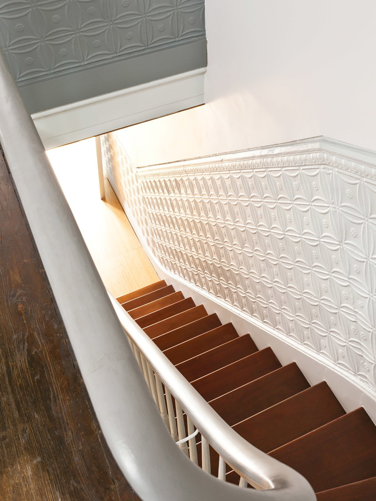 Staircase and Wood Tread The tin panels lining the stairs are original to the house.  Lounge from New Prospects