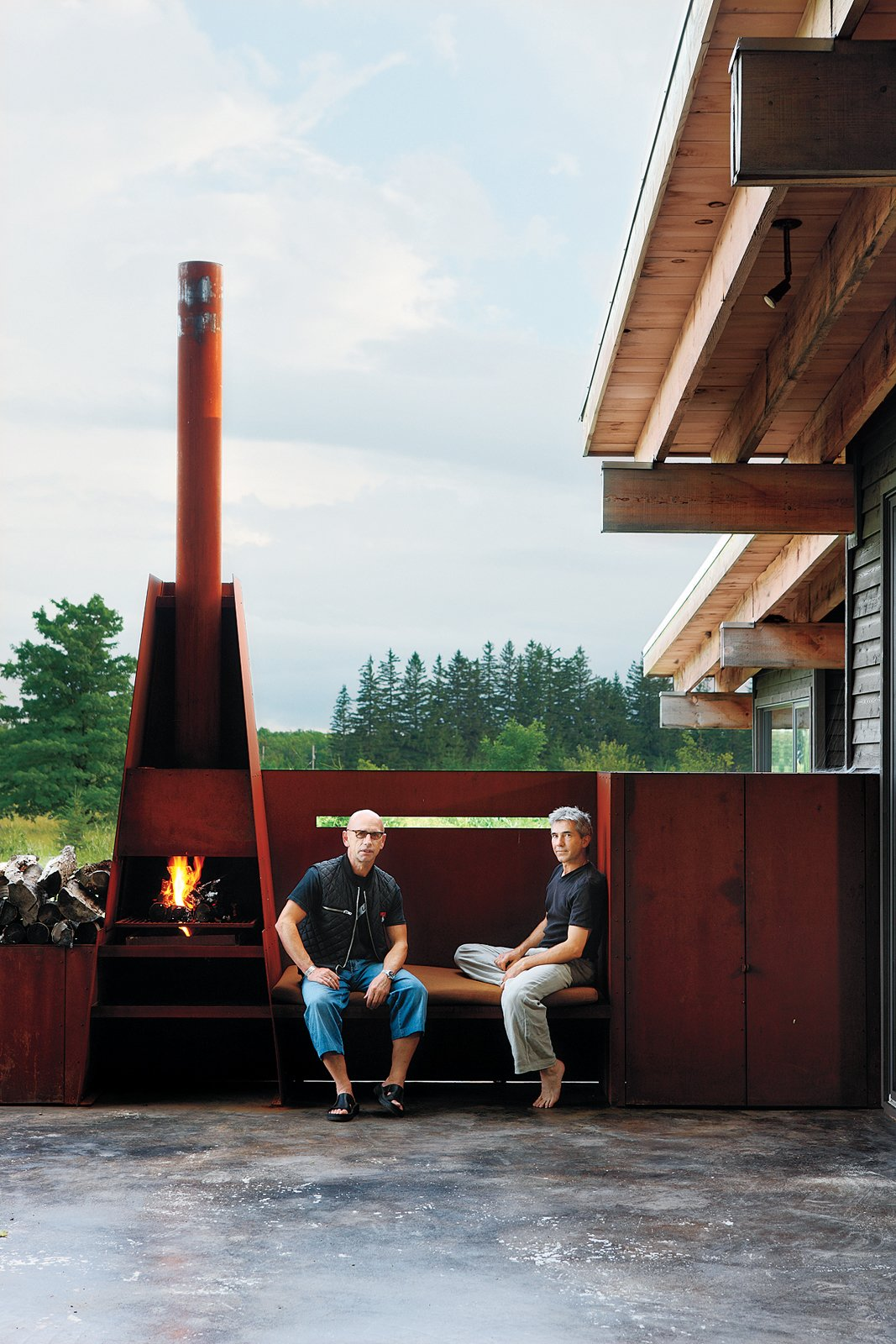 "Outdoor, Small Patio, Porch, Deck, and Back Yard Metals broker S. J. Sherbanuk (left) and designer James Campbell (right) created a new home in Collingwood, Ontario, with old scrap. ""Repurpose, refurbish, recycle"" was the guiding principle for the project. The modern, metal fireplace becomes a sculptural feature of an outdoor deck.  Seven Great Outdoor Spaces by Miyoko Ohtake"