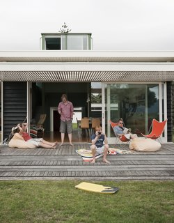 The Parsonson Residence, a modern beach house in New Zealand, features slide-away doors and a large patio perfect for sunbathing and looking out toward Kapiti Island. (And because of the mild Kiwi winter, this is one outdoor space that doesn't need to be packed up for winter.)