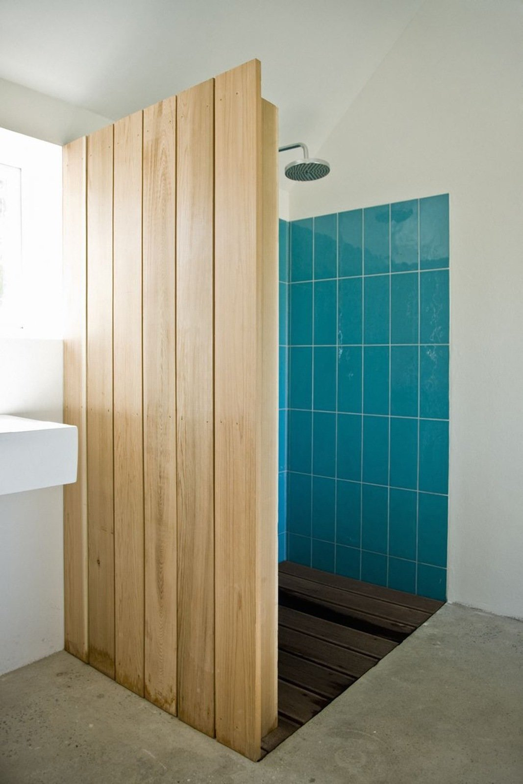 """Colored tiles in the shower are revealed behind a cedar wood wall. """"The sound of falling water on wood and the surrounding fields form the background,"""" say the architects. """"This was our way of introducing an immaterial idea of what luxury actually could be about.""""  Barn Renovation Ideas"""