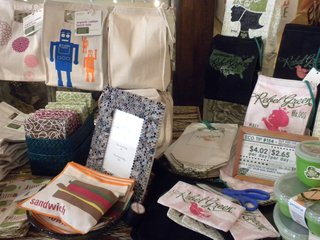 Signs with green tips speckle the store, like this one about reusable lunch bags that sits next to fabric sandwich bags and lunch totes by Graze Organic and Rebel Green.