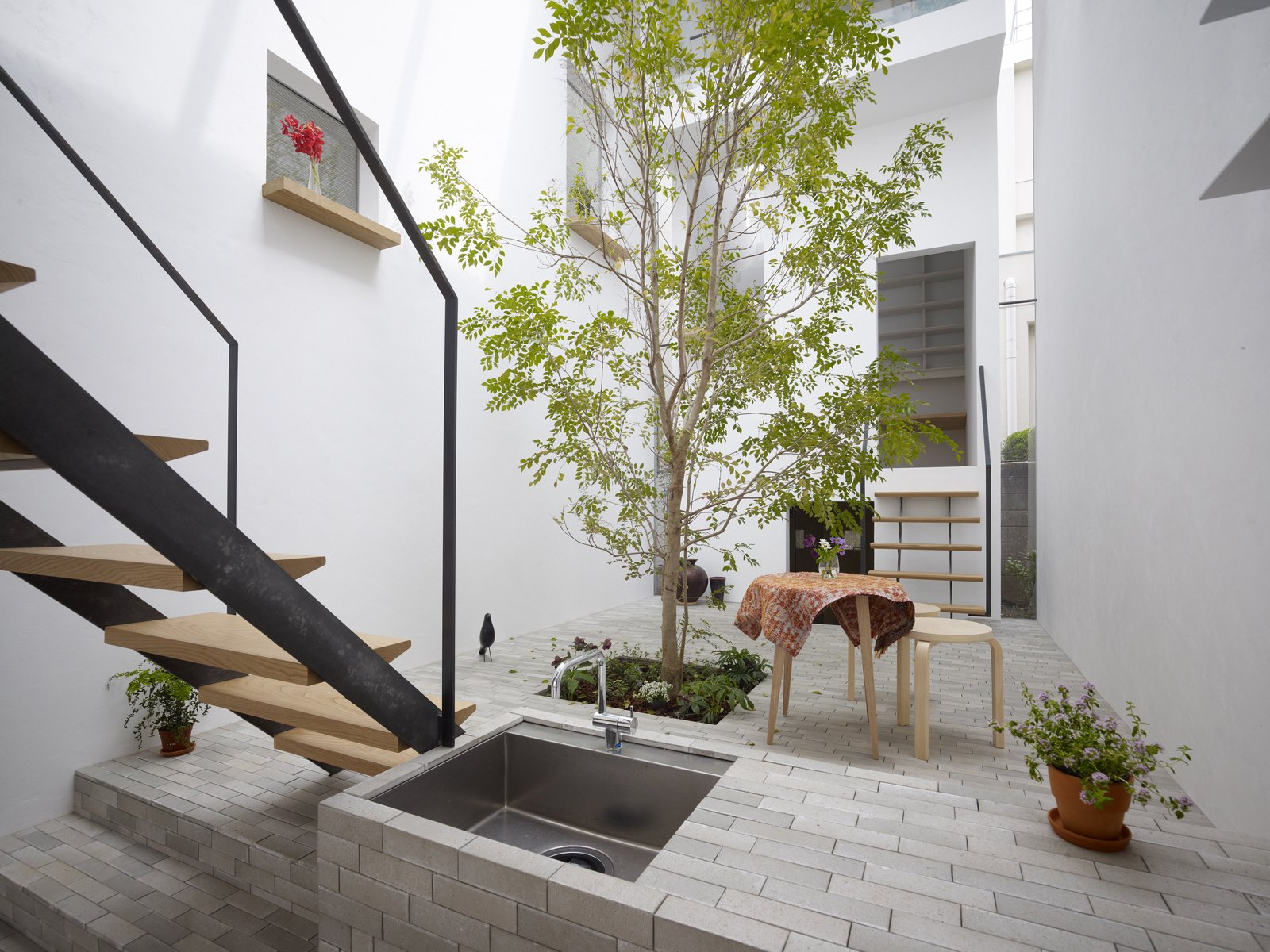 """We tried to achieve a space in which inside and outside co-exist together,"" architect Akira Mada says. ""As we walk around the house, at times we feel the space is totally outside while at other moments it is an interior. It's this co-existence that gives the residence its unique atmosphere.""  Ways to Incorporate Trees into Homes by Diana Budds from Great Indoors"
