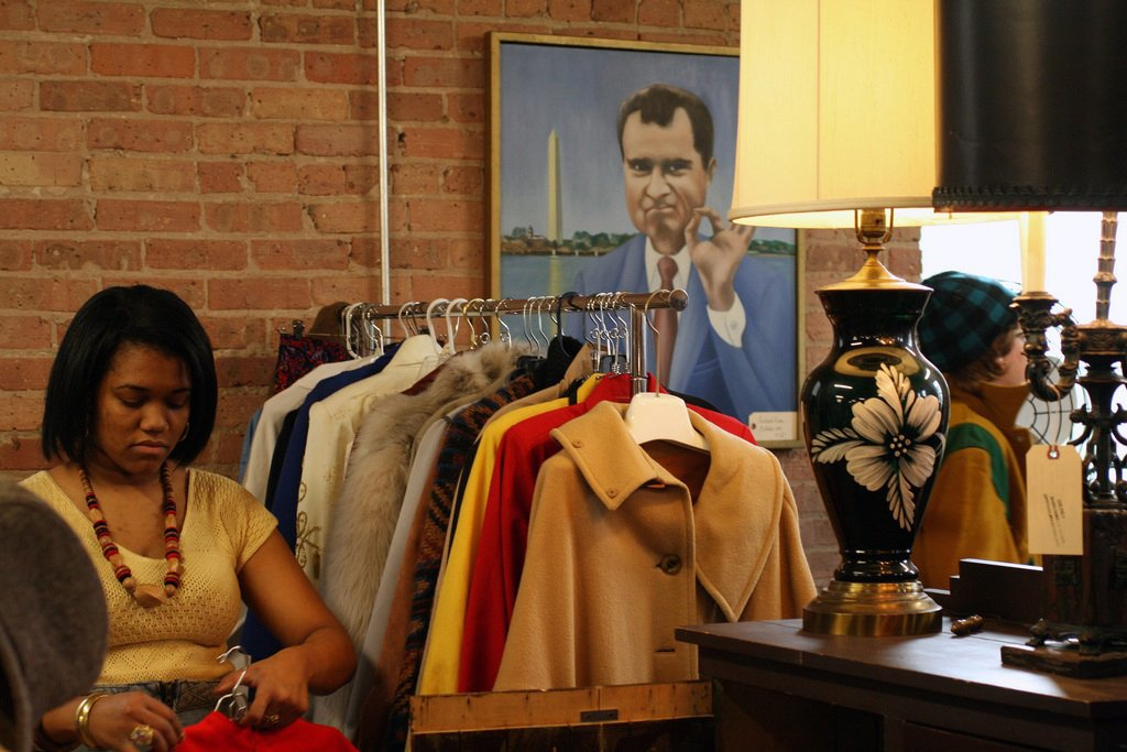 TVB is a-ok! A goofy portrait of President Nixon from Manly Vintage's booth keeps an eye on Jillian Knox of JJoules Vintage as she stocks a rack with fab vintage coats.   Photo by   Steven Pate  Photo 9 of 10 in More Finds from The Vintage Bazaar