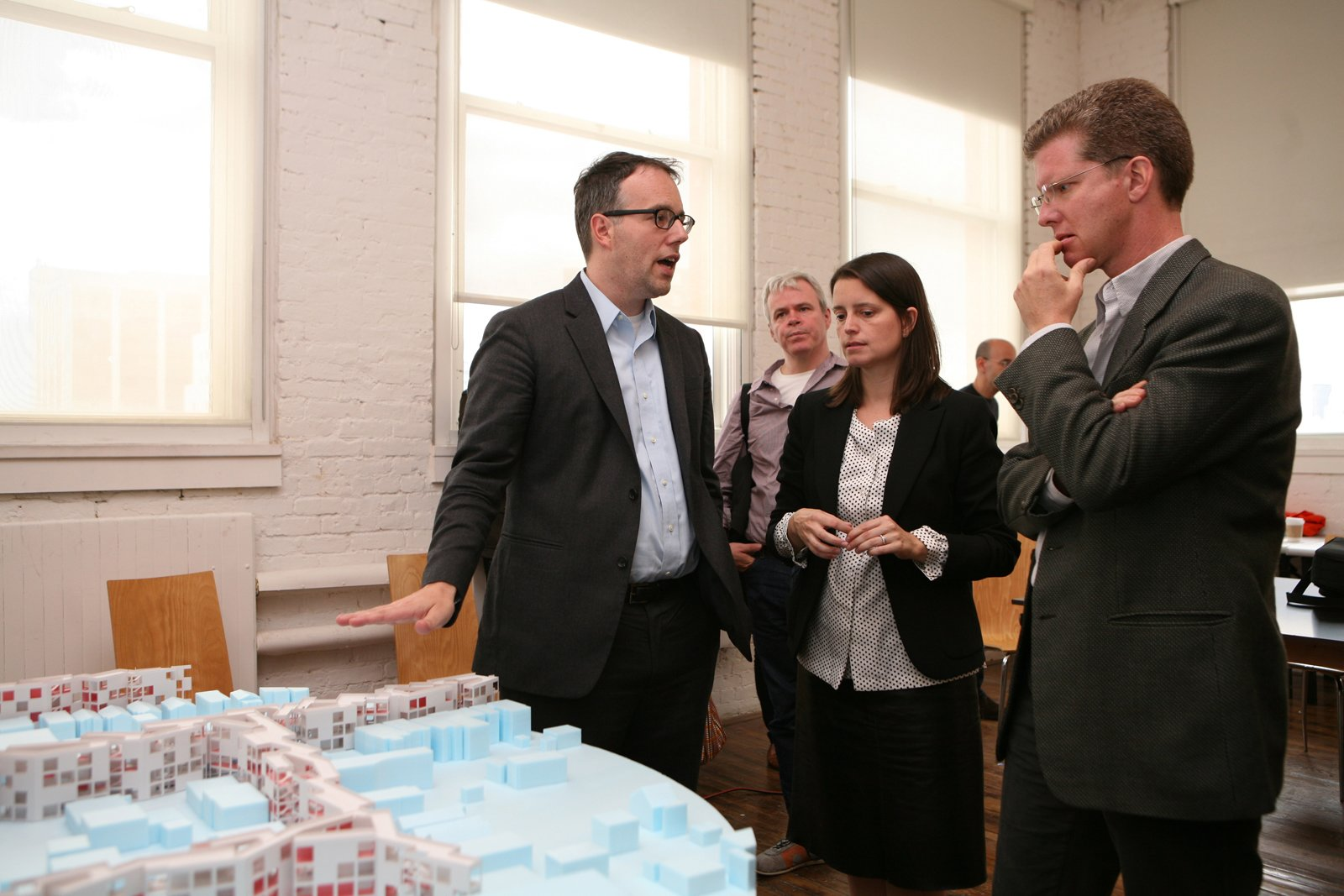 """U.S. Secretary of Housing and Urban Development Shaun Donovan (right) discusses MOS's proposal with Michael Merideth and Hilary Sample.  Photo 1 of 7 in """"Foreclosed"""" Open Studio at PS1"""