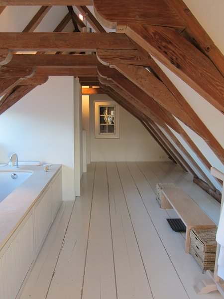 Bath, Undermount, Painted Wood, and Soaking A very steep and narrow flight of stairs led to my favorite part of the room: a big bathroom tucked into the attic, with original wooden beams arching overhead.  Best Bath Painted Wood Soaking Photos from The Dylan, Amsterdam
