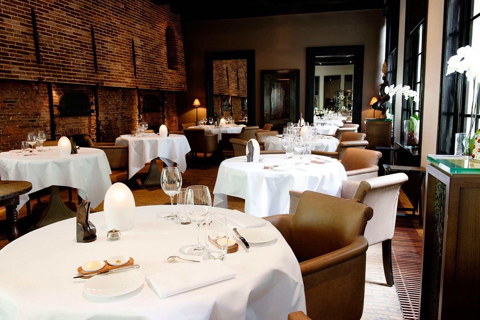 """The hotel's elegant Michelin-starred restaurant, Vinkeles, was formerly a bakery, in operation between 1787 to 1811 and run by the """"Catholic Old and Poor People's Office."""" The sunken dining room is surrounded by original 18th century ovens.  The Dylan, Amsterdam by Jaime Gillin"""